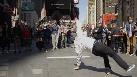NEW YORK - APR 11, 2015: breakdancer flipping and twisting in crowded Times Square in slow motion 4K Manhattan NY. Times Square is a major commercial intersection in NYC.