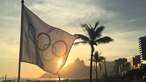 RIO DE JANEIRO, BRAZIL - FEBRUARY 12, 2015: An Olympic flag flutters in the wind in front of the sunset skyline at Ipanema Beach.