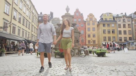 Couple walking holding hands in city of Stockholm, Sweden, Europe. Happy multiracial young couple walking outside on Stortorget big square in Gamla Stan, the old town. Scandinavian man, Asian woman.