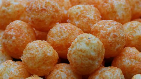Cheese Balls Chips rotation. Close up Cheesy Puffs Snack Food Rotating. Macro american cheese ball 4k video. Drink and food background. food texture. fast food concept full hd with copy space.