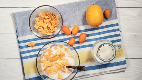 Healthy breakfast of cornflakes with milk on white wooden table. Top view on ingredients and preparation of cornflakes breakfast, stop motion, animation.