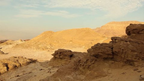 View of rocky landscape in Timna park, Sandstone cliffs, stone desert, blue sky with clouds, sand and stone mountains, Israel