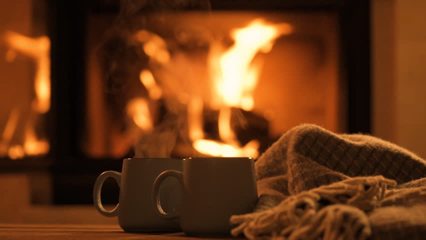 Steam from a cups with a hot cocoa on the fireplace background.   | Shutterstock HD Video #1006610437