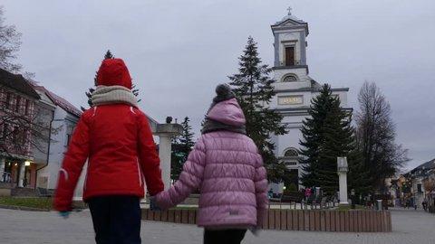 Two little beautiful girls walk near Evangelical Church of Holy Trinity on Namestie Egidia Street, Poprad, Slovakia.