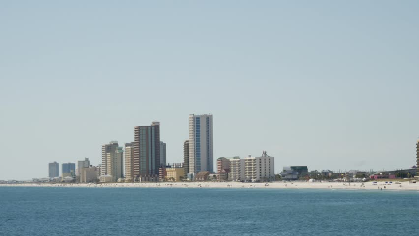Zooming out shot of modern residential buildings and hotels on the sunny shore of an idyllic travel destination at the seaside