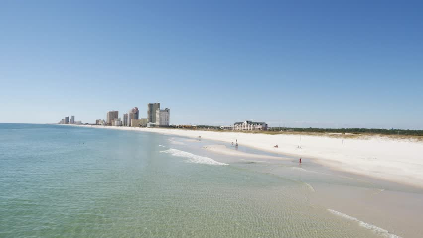 View of a sandy beach with urban high-rise buildings in the distance and a calm blue ocean on a sunny day in a static clip