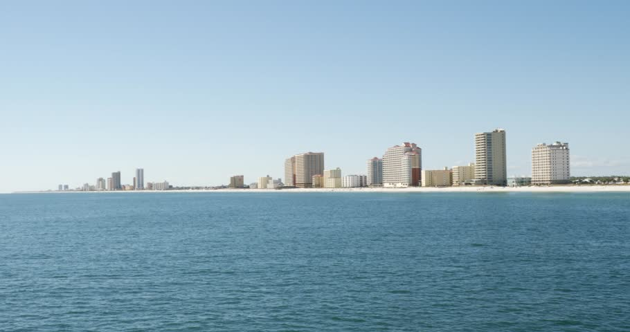 Panoramic view of a luxury resort with waterfront buildings along the coastline against clear blue sky in a sunny day