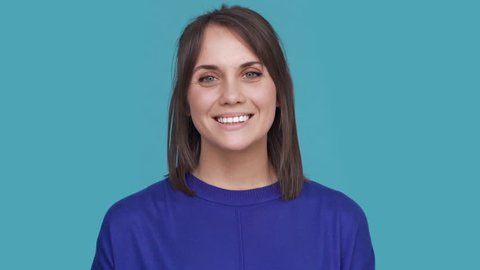 Portrait of cute woman smiling with white perfect teeth saying yes and nodding positively meaning agreement over blue background. Concept of emotions