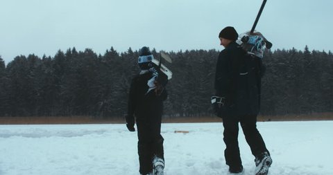 TRACKING Father and son walking towards outdoor rink on a frozen lake to play pond hockey. 4K UHD