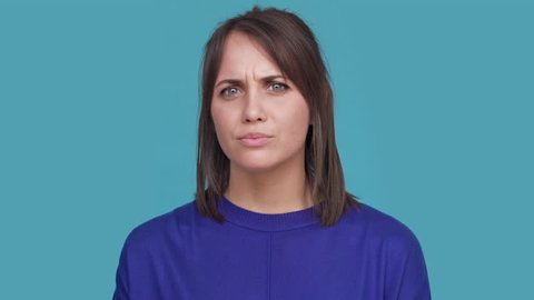 Portrait of serious young female expressing displeasure or disinterest with facial expressions meaning not good over blue background. Concept of emotions