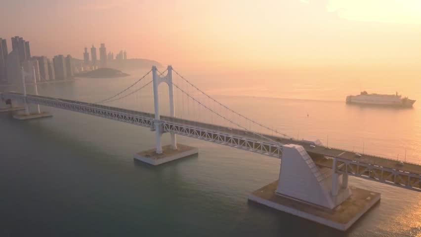 Aerial view of Gwangan Bridge and Haeundae Beach with Sunrise in the morning in Busan, South Korea   Shutterstock HD Video #1006716487
