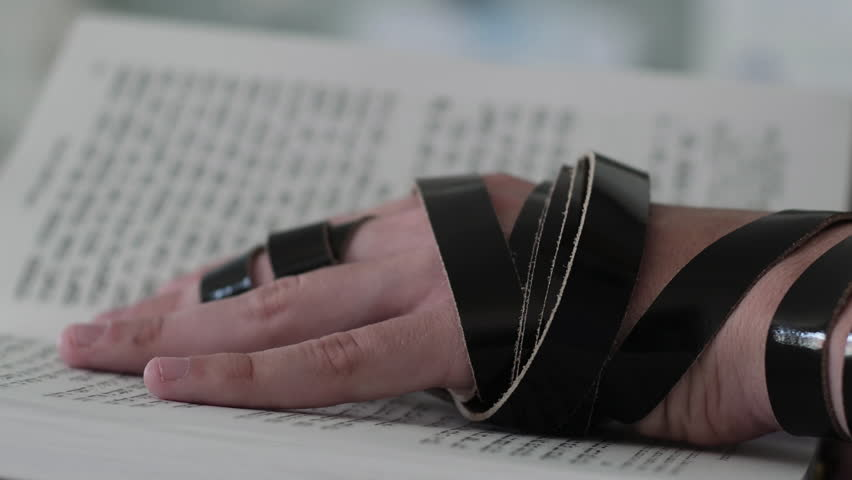 Hand of young jewish man with a tefillin on his arm, holding a psalms book, while reading a pray at a jewish ritual.