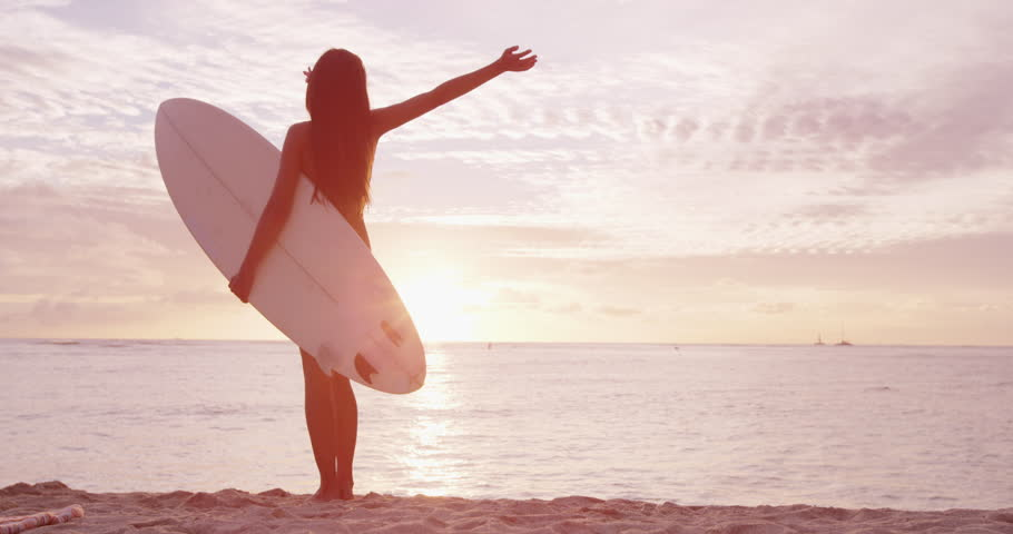 Surfer girl surfing happy and serene looking at beach sunset holding surfboard. Female surfer woman looking at water with arms outstretched living healthy active lifestyle. SLOW MOTION shackycam