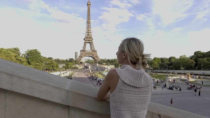 4K video of a young woman wandering in the streets of Paris near the Eiffel Tower, contemplating the view and enjoying travel. People cities traveling concept | Shutterstock HD Video #1006729987