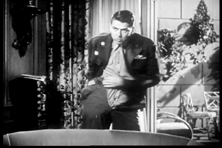 CIRCA 1980 Ronald Reagan struggles to fasten his pants on set.