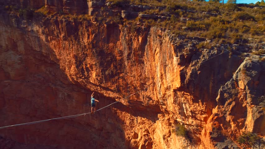 Brave Man Slacklining , highlining above a big canyon . Nature Adventure and leisure sport . Mountain Balance Extreme Hiker Walking Happy, 4k aerial slow motion