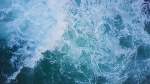 Top view of ocean blue waves crashing coastline cliff drone footage