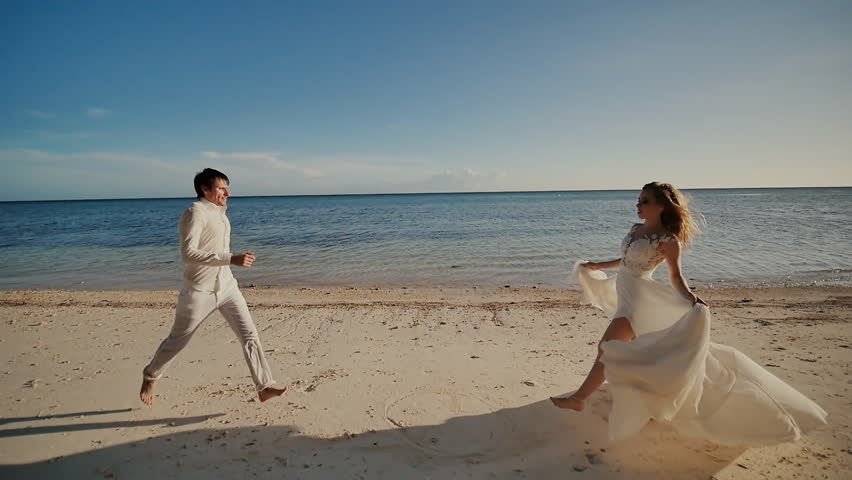 The groom and beautiful bride run barefoot to each other along the sandy shore of the ocean. Happy together. A tropical wedding. Shooting in motion.