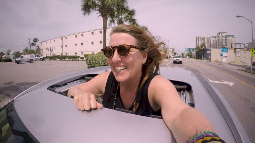 Happy attractive blond woman standing through a sun roof smiling and looking at the camera taking a selfie while being driven in a car