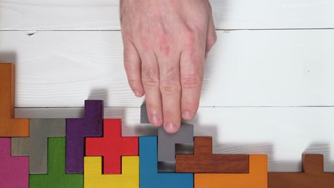 Top view on man's hand playing with colorful wooden blocks on the white wooden table background. The concept of logical thinking.