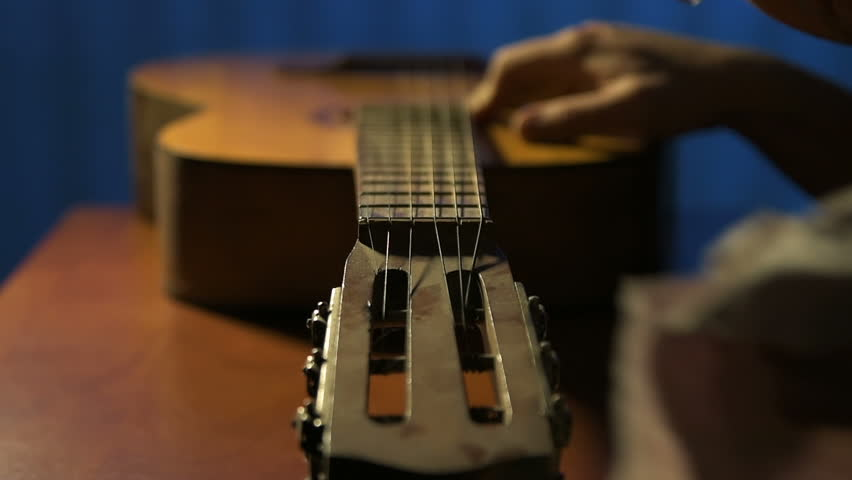 Former guitarist gently rubs head of fretboard of old acoustic guitar | Shutterstock HD Video #1006805137