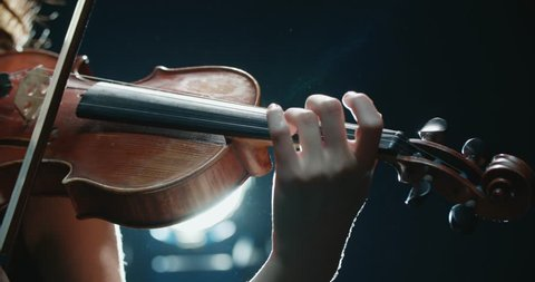 detail shot, performance of violinist girl on stage, light, dark background