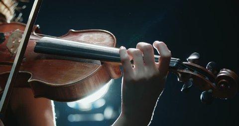detail shot, performance of violinist girl on stage, light, dark background