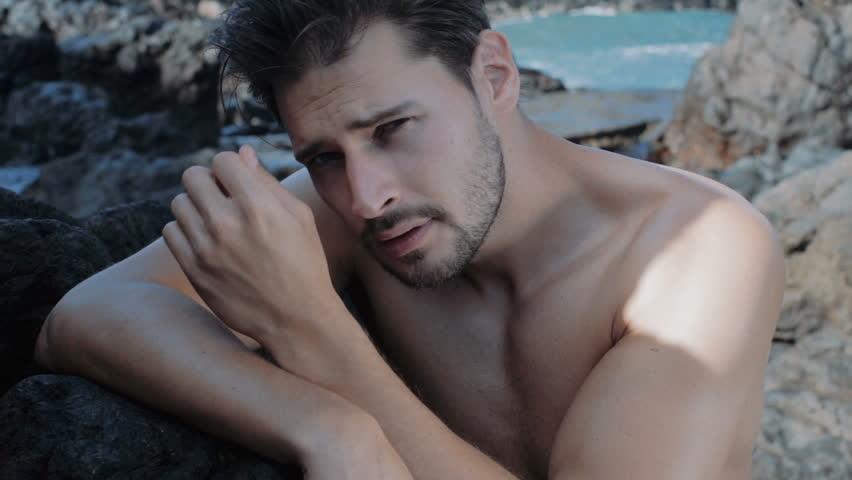 Stylish seducer man at posing at rocky sea shore, slow motion clip
