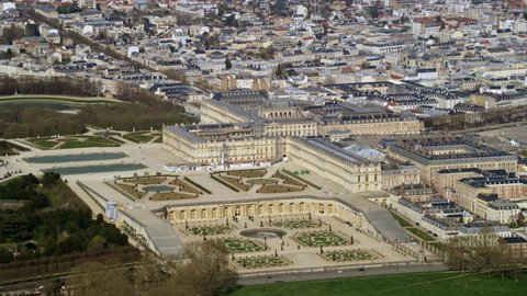 4K Aerial view above the palace of Versailles with landscaped gardens & the surrounding area