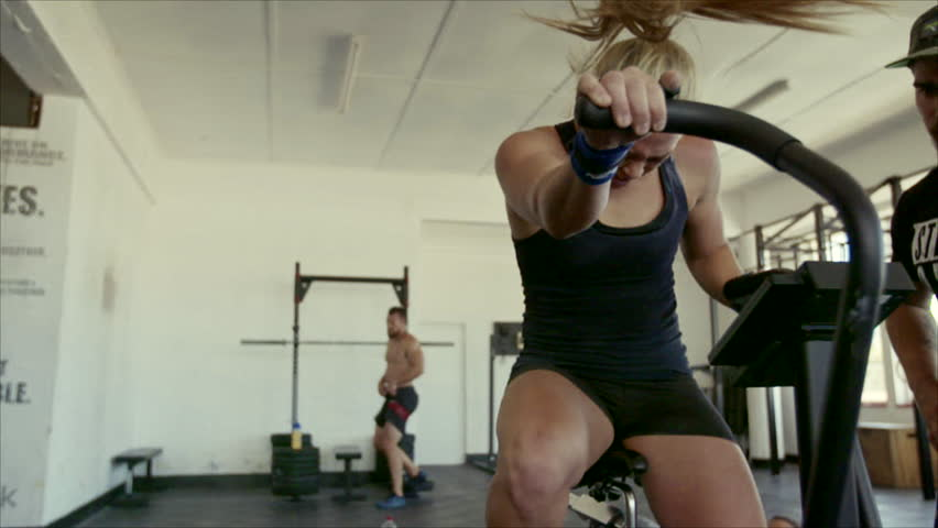 Description :- Female athlete doing intense workout on gym bike with coach. Fitness woman spinning stationary bicycle in cross fit gym with male personal trainer.