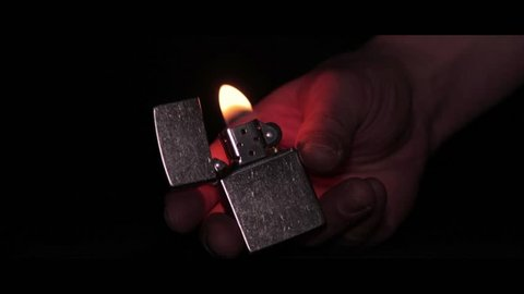close-up of the opening and the burning of iron Zippo lighter on a black background