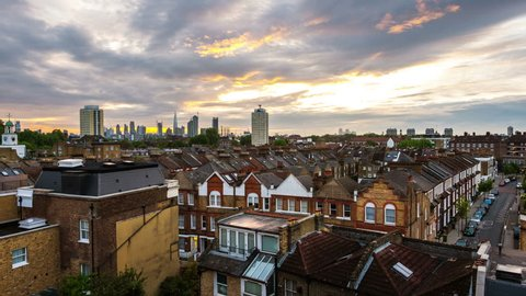 London, UK. Aerial view of residential district with modern skyscrapers at the background in London, UK. Heavy clouds over the city. Time-lapse at sunrise
