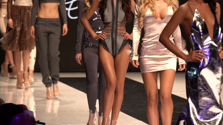 Female models walk the runway in different dresses during a Fashion Show. Fashion catwalk event showing new collection of clothes. In a row. Slow motion x5
