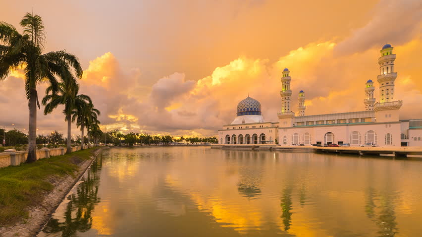 Dramatic Time lapse of sunset and scattered clouds at a mosque in Likas, Kota Kinabalu, Sabah, Malaysia. 4K resolution, 4096 x 2304. Zoom In Motion Timelapse. Day to Night.