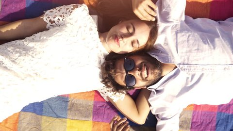 Happy lovely young couple lying on colorful blanket in the park looking at the sky pointing clouds romantic with guitar sunglasses beautiful attractive girl top view rotating camera slow motion
