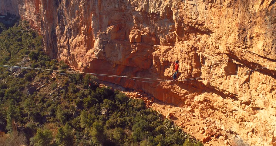 Brave Man Slacklining , highlining above a big canyon . Nature Adventure and leisure sport . Mountain Balance Extreme Hiker Walking Happy, 4k aerial cinematic footage