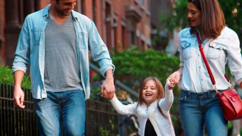 Couple swing their daughter as they walk in street, mid section