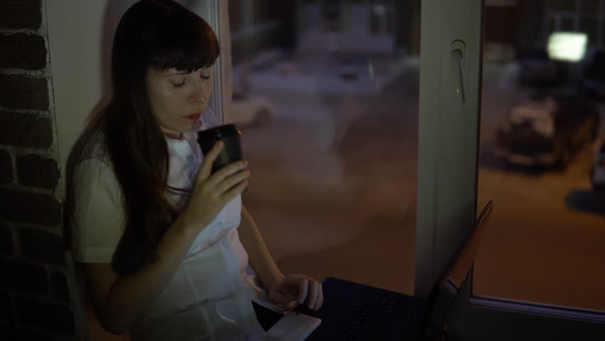 A business woman sits on the windowsill drinks cofee and works on a laptop, outside the window in the street a road with a busy traffic. | Shutterstock HD Video #1006880287
