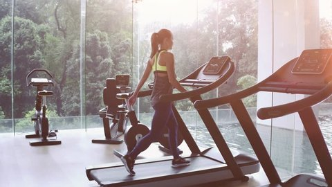 Cute Asian girl on treadmill at gym. Panoramic window, healthy fitness lifestyle concept
