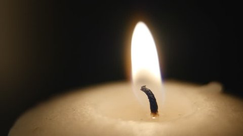 Candle blown out. The candle is lit and extinguished in the dark. White candle. Black background. close up