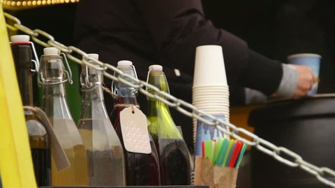 Seller pouring hot mulled wine to customers at roadside cafe, small business