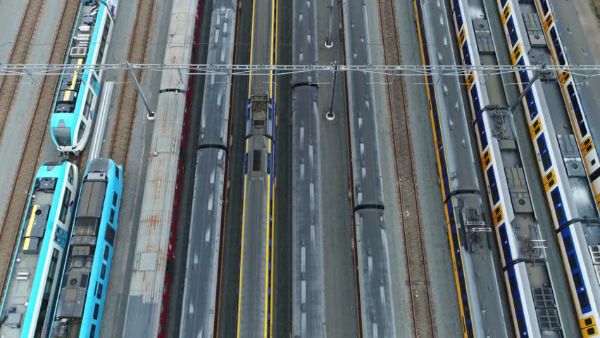 Aerial top down view of railway hub and parked passenger trains next to each other moving slowly over the rail vehicles with different colors beautiful rail network scene 4k high resolution footage | Shutterstock HD Video #1006983247