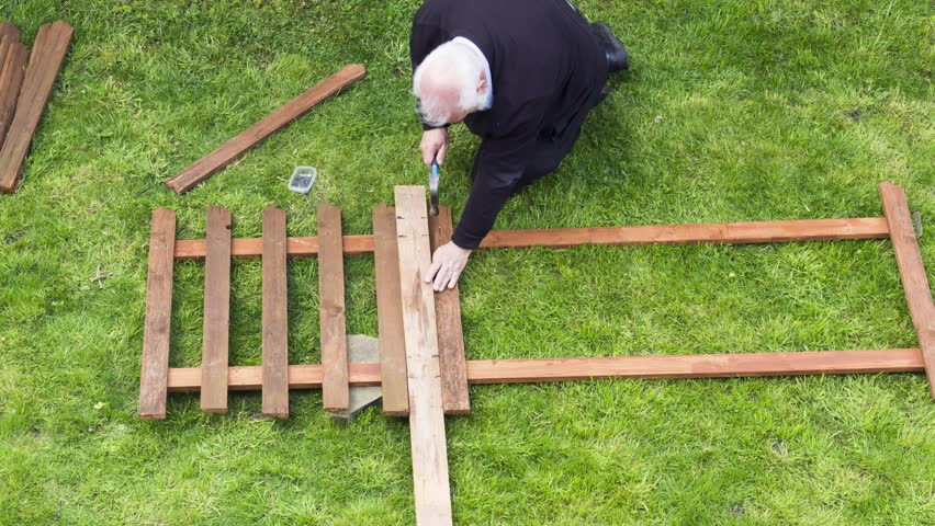 High angle viewpoint timelapse of middle aged man constructing a wooden picket fence panel from scratch using hammer and nails on lengths of timber and wooden slats.