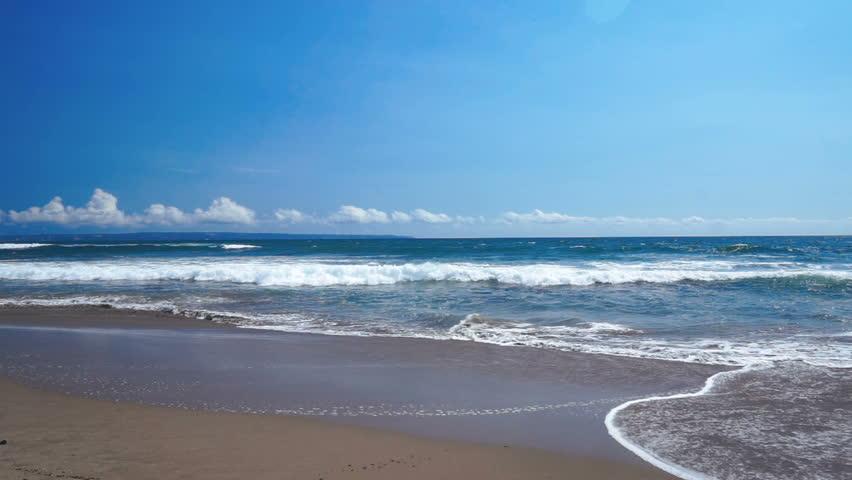 Asian coast line with ocean waves with foam gently washing grey sand beach