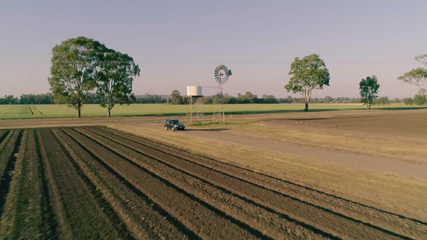 Aerial / Drone Shot Of Subaru Forrester, With Female Farmer And Agronomist Driving Through Farming Property And Crop Field At Sunrise