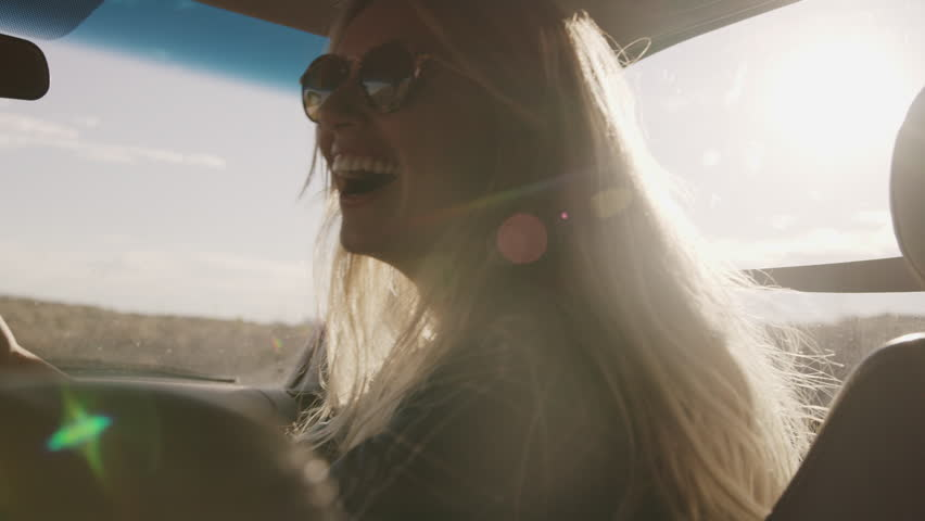 Laughing woman in car holding cell phone and pointing in slow motion / Hanksville, Utah, United States