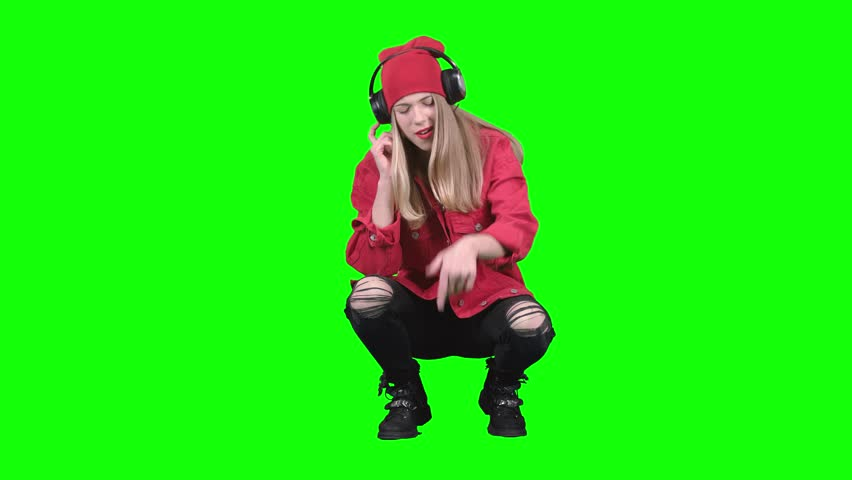Girl sitting on her haunches and listening to music on headphones. Green screen