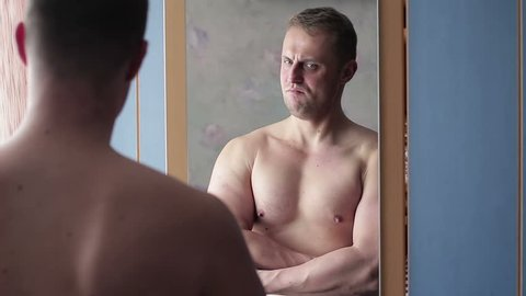 Funny narcissist guy straining his muscles in front of the mirror