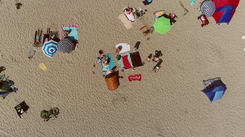 Aerial top down view flight over recreational beach with many people sun bathing and enjoying them on the warm hot sand also showing colorful parasols and beach towels on warm hot summer day 4k