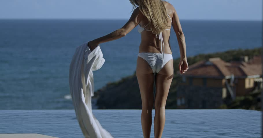 attractive woman getting into the swimming pool at villa with ocean view